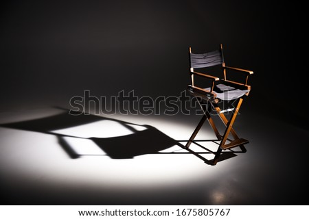 Directors chair stands in the beam of light. Space for text. Vacant chair. The concept of selection and casting. Shadow and light. Royalty-Free Stock Photo #1675805767