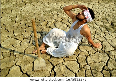 A suffering of an Indian farmer - A farmer sits upset in his dry and cracked agriculture field and look towards sky for rain due to heavy drought. #1675832278