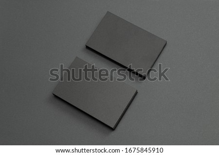 2 stacks of black blank textured business cards on dark paper background, us size 3.5 x 2 inches, as template for design presentation.