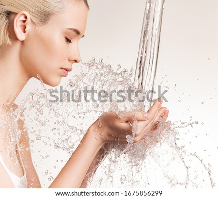 Photo of  young woman with clean skin and splash of water. Blonde woman with drops of water near her face. Spa treatment. Girl washing hands with water. Water and body.  #1675856299
