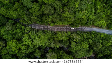 Aerial view asphalt road and green forest, Forest road going through forest with car adventure view from above, Ecosystem and ecology healthy environment concepts and background. Royalty-Free Stock Photo #1675863334