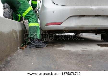 RUSSIA, MOSCOW-MARCH 13, 2020: Tow truck lifting the car for improper parking. The utility service removes the wrongly parked car.Image can be used for topics like traffic offense. #1675878712