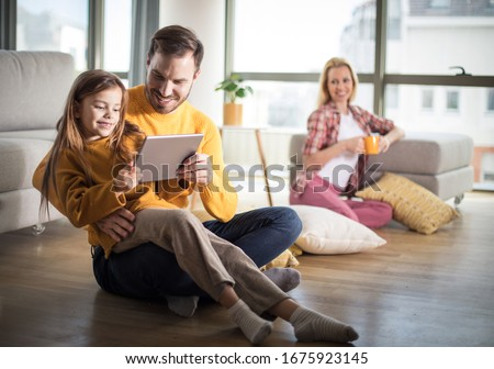 Let's watch a cartoon together. Family at home. Father and daughter using digital tablet.