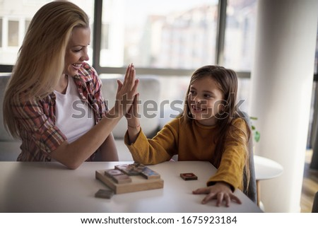 We are the perfect team. Mother and daughter playing at home. Focus on background. #1675923184