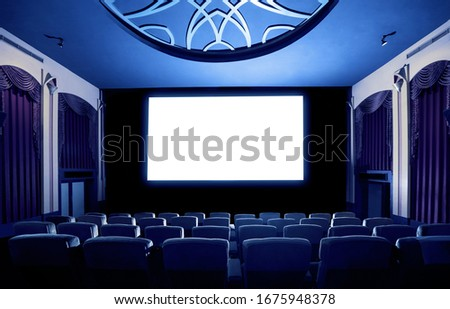 Cinema theater screen in front of seat rows in movie theater showing white screen projected from cinematograph. The cinema theater is decorated in classical style for luxury feeling of movie watching. #1675948378