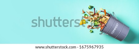 Peeled vegetables in white compost bin on blue background. Trash bin for composting with leftover from kitchen on blue background. Top view. Recycling scarps concept. Sustainable and zero waste Royalty-Free Stock Photo #1675967935