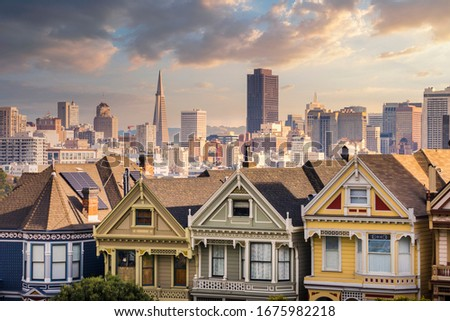 Seven sisters houses in San Francisco with Transamerica Pyramid on the background. Alamo Square, San Francisco, California, USA