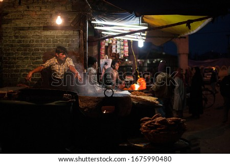 SRINAGAR, INDIA - APRIL 13: Unidentified Indian vendors selling food at Srinagar local market at night on Apr 13, 2014 #1675990480