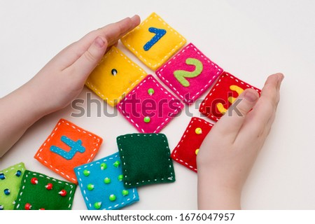 Home made game: find the right pair. Different color stuffed felt square with numbers and matching domino style dots. Early education, learning numbers. Royalty-Free Stock Photo #1676047957