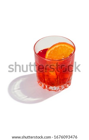 Negroni cocktail is contained in a low crystal glass with an orange slice and ice cubes. The showy illustrative picture is made on the white backdrop.