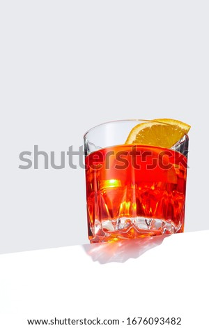 Negroni cocktail is contained in a low crystal glass with orange slices and ice cubes and isolated on a table edge. The showy illustrative picture is made on the gray backdrop.