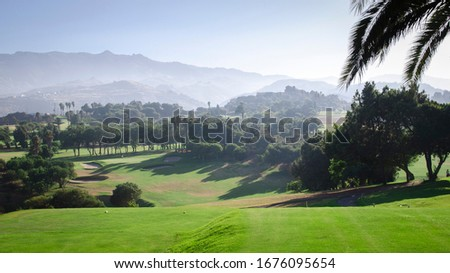 Landscape picture of a golf course in a volcanic island with a volcano in the background. Canary Islands, Spain