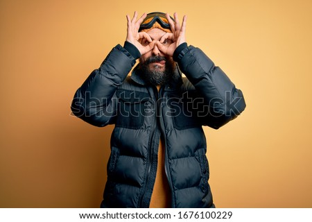 Handsome skier bald man with beard skiing wearing snow sportswear and ski goggles doing ok gesture like binoculars sticking tongue out, eyes looking through fingers. Crazy expression. #1676100229