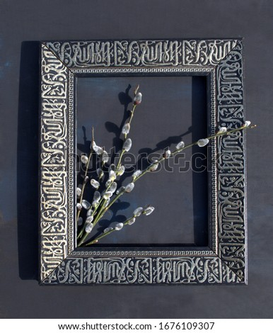 On a black background in a dark frame for the picture are live willow twigs by Palm Sunday