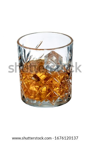 Old Fashioned Whiskey is contained in a crystal lowball glass with ice cubes. The showy illustrative picture is made on the white backdrop.