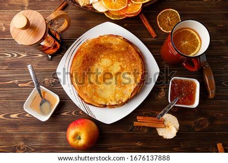 Maslennitsa food with bliny dried fruits apple tea pot honey and jam Royalty-Free Stock Photo #1676137888