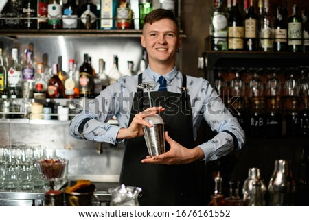 young smiling barman preparing glass and shaker to make cocktail. Shelves with bottles of alcohol in background. #1676161552