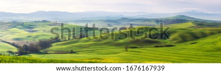 Amazing Tuscany panoramic landscape with green rolling hills in spring sunny morning Royalty-Free Stock Photo #1676167939