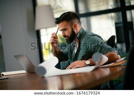 Young businessman working with laptop at office. Businessman sitting at office desk working on laptop computer. #1676179324