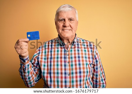 Senior handsome hoary customer man holding credit card to finance payment with a happy face standing and smiling with a confident smile showing teeth
