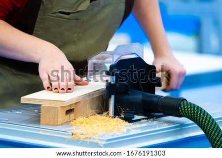 Joinery. The girl is engaged in woodworking. Woodworking machine with vacuum cleaner. Equipment carpentry workshop. Production of furniture to order. Woodworking as a hobby. #1676191303