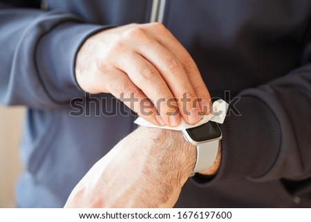 man hands disinfecting smart watch, eliminating germs coronavirus bacteria #1676197600