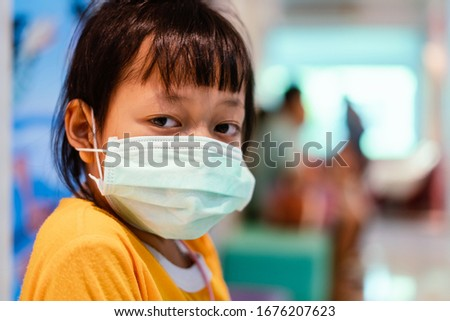 Asian little girl sitting in a hospital and wear  medical mask with sad eyes and hope . Coronavirus Covid-19 concept. #1676207623