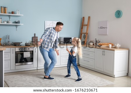 Man and his little daughter dancing in kitchen #1676210671