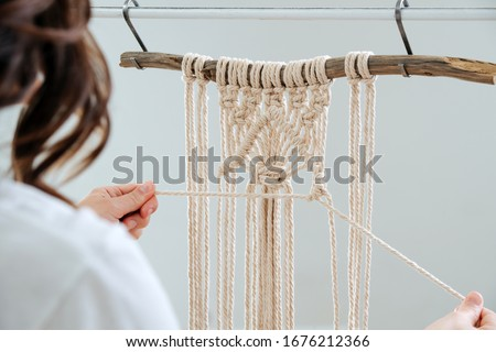 The base knots of macrame, the view from behind the shoulder close-up of the girl's hands, she ties knots #1676212366