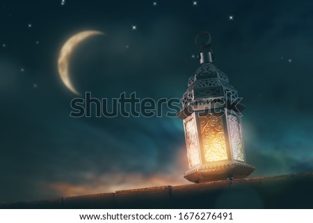 Ornamental Arabic lantern with burning candle glowing at night. Festive greeting card, invitation for Muslim holy month Ramadan Kareem. #1676276491
