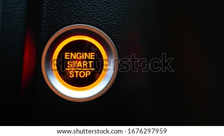 Car dashboard with focus on red engine start stop button, car interior details. button engine start and engine stop, Car engine push start stop button ignition remote starter. #1676297959