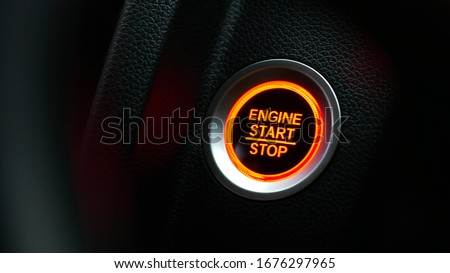 Car dashboard with focus on red engine start stop button, car interior details. button engine start and engine stop, Car engine push start stop button ignition remote starter. #1676297965