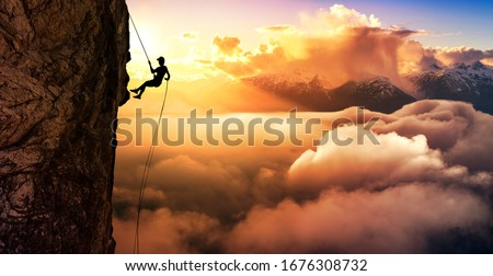 Silhouette Rappelling from Cliff. Beautiful aerial view of the mountains during a colorful and vibrant sunset or sunrise. Landscape taken in British Columbia, Canada. composite. Concept: Adventure #1676308732