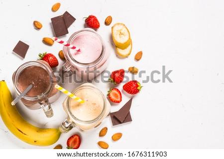 Set of milkshake or smoothie in mason jars. Banana, chocolate and strawberry milkshakes with nuts. Summer dessert. Healthy food. Top view. #1676311903