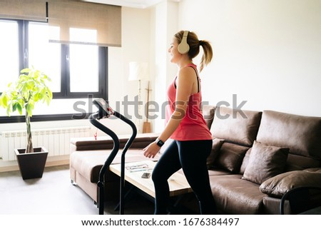 Beautiful caucasian blonde woman exercises on a treadmill in her living room. Workout. #1676384497