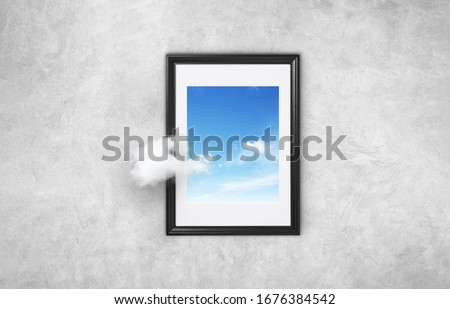 Beautiful picture with a black frame with blue sky and cloud on a gray concrete wall. Concept think differently. Going beyond. Think outside the box surreal minimal concept