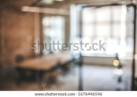 Blurred office interior space background. Blurred interior of modern office workplace a workspace design without partition decorate with black, white and wooden furniture Royalty-Free Stock Photo #1676446546
