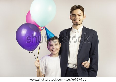 Two guys joyfully posing during their birthday. Two guys with balloons. They are smiling. Banner.Place for text