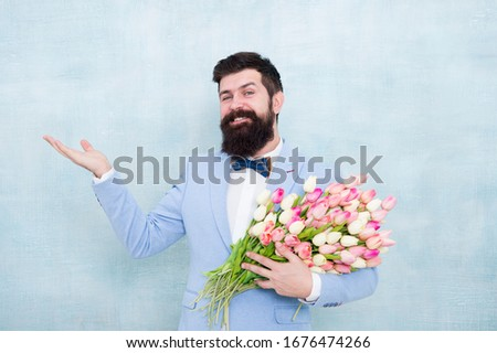 Choose and order gift. Bearded man with fresh flowering gift. Happy hipster with tulip bunch. Floral gift for Valentines day. Valentines gift for women. Valentine man hold empty hand for copy space. #1676474266