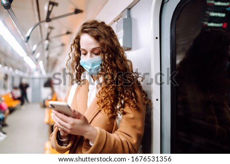 Girl in protective sterile medical mask on her face with a phone in a subway car. Woman using the phone to search for news about coronavirus. The concept of preventing the spread of the epidemic. #1676531356