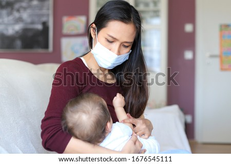 Mother breastfeeding her newborn baby in her arms while wearing surgical face mask sick concept during corona virus, covid-19 pandemic or allergy. Asian mommy sickness with child. #1676545111