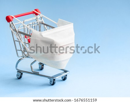 Shopping cart with protective medical mask against coronavirus. Safe and online shopping on quarantine concept. Light blue background, copy space. Royalty-Free Stock Photo #1676551159