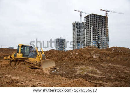 Dozer working at construction site. Bulldozer for land clearing, grading, pool excavation, utility trenching and foundation digging. Crawler tractor and earth-moving equipment #1676556619
