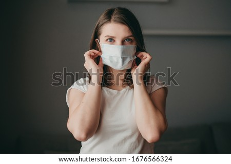 Young blonde white european blue-eyed woman at home on quarantine with medical mask on gray background. Coronavirus, illness, infection, quarantine, surgical bandage. #1676566324