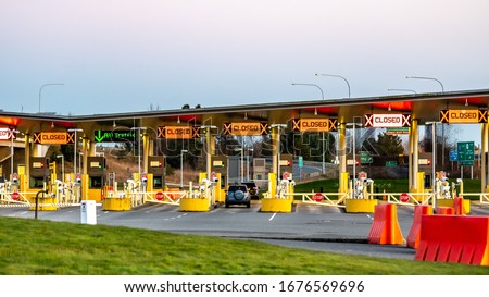 US/Canada Border, Peace Arch, Washington State, USA. Empty border lanes at crossing between US and Canada. Royalty-Free Stock Photo #1676569696