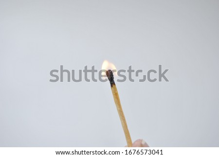 Burning safety-match with fire. Isolated on white background. Burning match in male hand. Burning match detail on white background. Burning match-stick detail. #1676573041