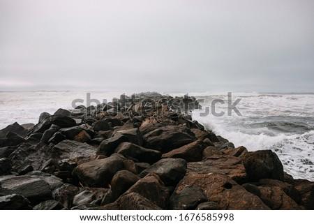 Rocky pier in pacific ocean. Pacific Northwest. Rocky breakwater. Birds resting on the breakwater.  Royalty-Free Stock Photo #1676585998