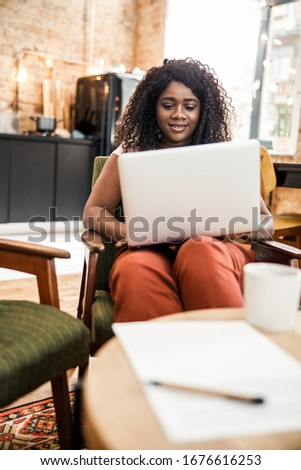 Charming young woman working on laptop and smiling stock photo #1676616253