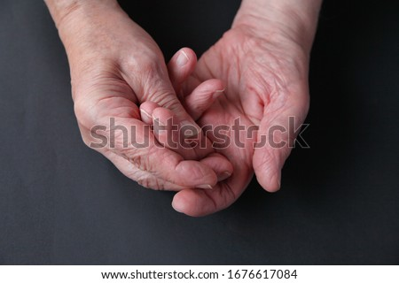 An older man holds his sore fingers on a dark background with room for text #1676617084