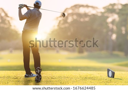Golfer he's golfing in sunlight of the morning. View from the back. Royalty-Free Stock Photo #1676624485